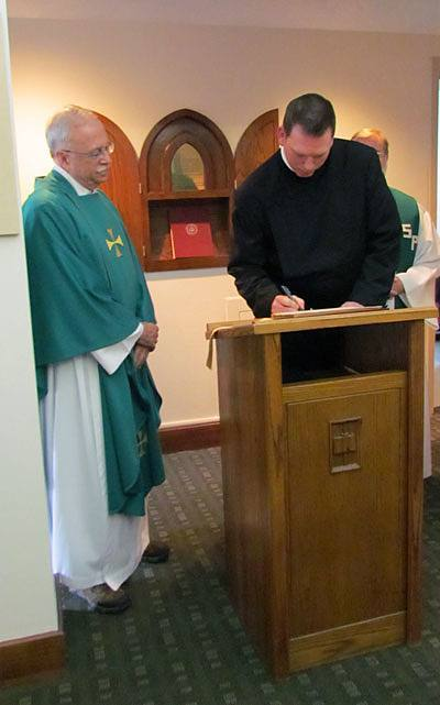 Steven Petroff, CSP, signs the contract in which he promises to live by the Paulist constitution for the next 12 months after making  his first promise with the Paulist Fathers. Paulist President Father Michael McGarry (left) looks on.