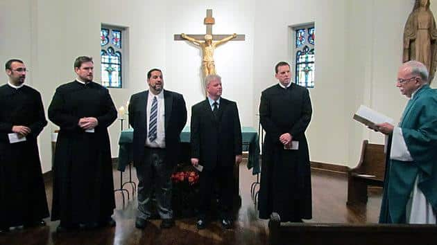 As Paulist President Father Michael McGarry (far right) looks on, the five men make their first promise in the Paulist community. The nem are: Matthew Berrios, CSP (left), Stuart Wilson-Smith, CSP, Ryan Casey, CSP, Mark Alblinger, CSP and Steven Petroff, CSP.