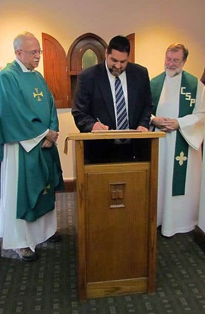 Ryan Casey, CSP, signs the contract in which he promises to live by the Paulist constitution for the next 12 months after making  his first promise with the Paulist Fathers. Paulist President Father Michael McGarry (left) and Novice Director Father Richard Colgan, CSP (right), look on.