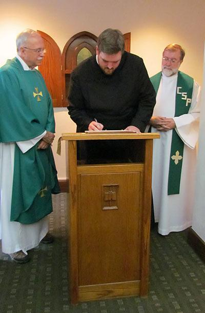 Stuart Wilson-Smith, CSP, signs the contract in which he promises to live by the Paulist constitution for the next 12 months after making  his first promise with the Paulist Fathers. Paulist President Father Michael McGarry (left) and Novice Director Father Richard Colgan, CSP (right), look on.