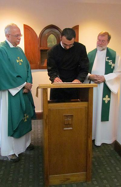 Matthew Berrios, CSP, signs the contract in which he promises to live by the Paulist constitution for the next 12 months after making  his first promise with the Paulist Fathers. Paulist President Father Michael McGarry (left) and Novice Director Father Richard Colgan, CSP (right), look on.