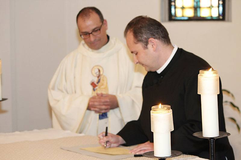 Daniel Arthur, CSP, signs the book listing him as a member of the Paulist community after making his first promise as Father Eric Andrews, president of the Paulist Fathers, looks on.