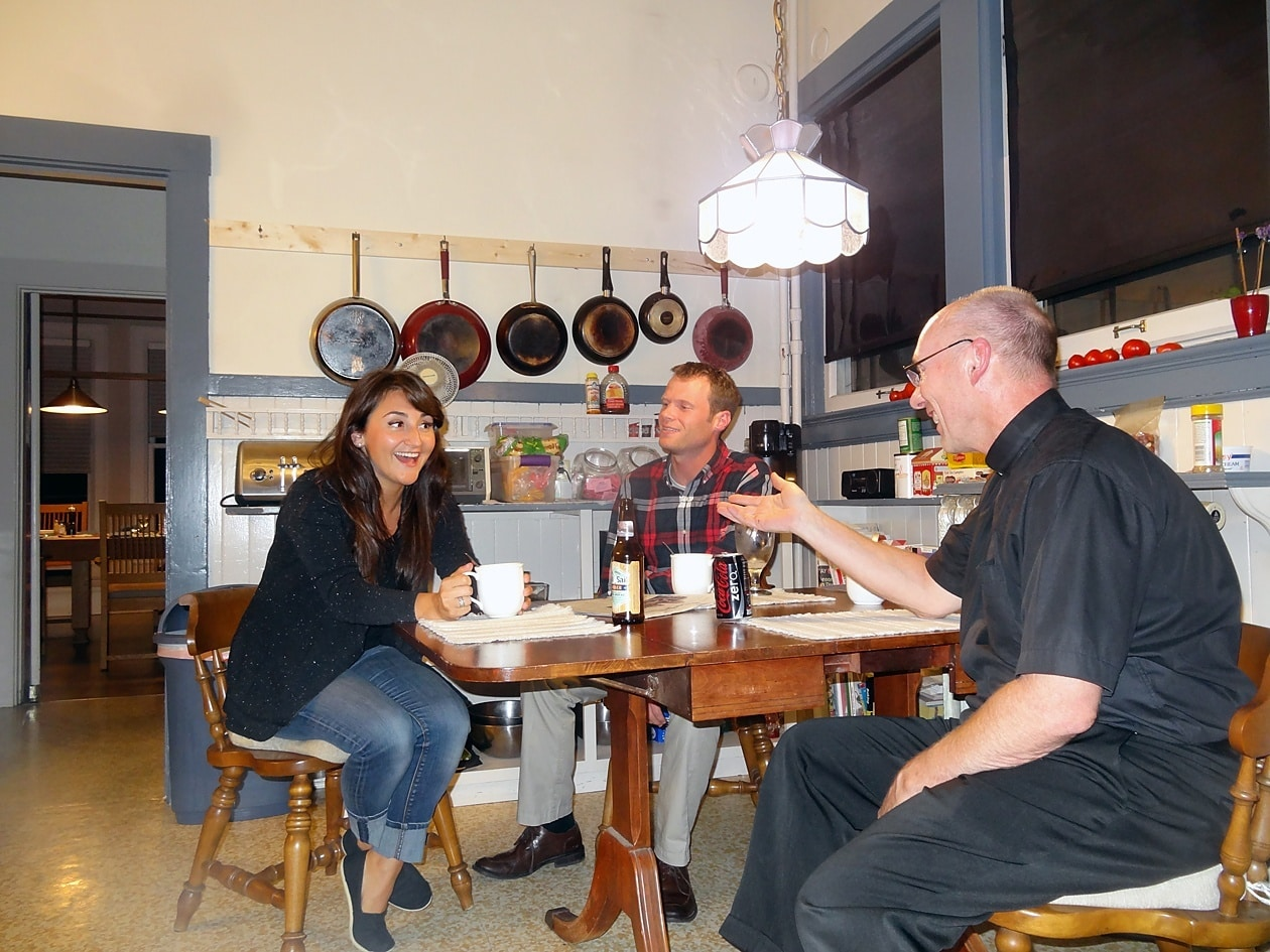 Adrienne Jarvis (left), Tommy Manning and Father Bill Edens strategize on how to reach young adults in the kitchen of the St. Philip Neri rectory in Portland, Ore.