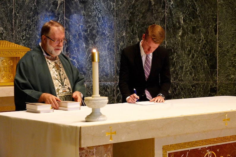 chris-signing-at-altar
