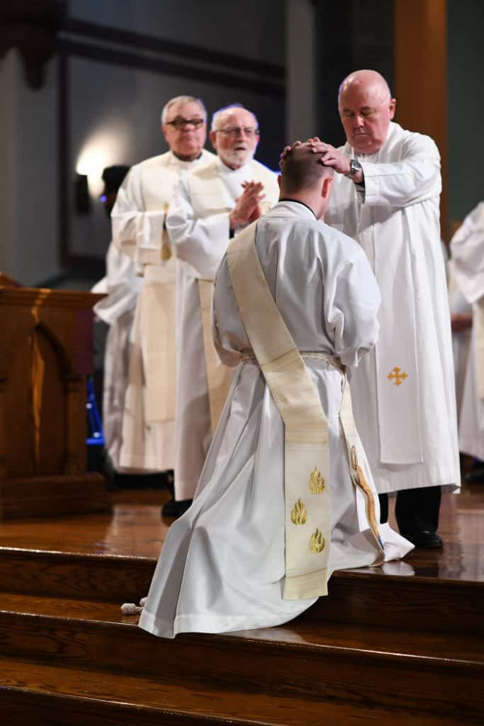 Paulist Fr. Tim Tighe prays over Paulist Fr. Mike Hennessy at the Mass in May, 2018, at which Fr. Mike was ordained a priest.