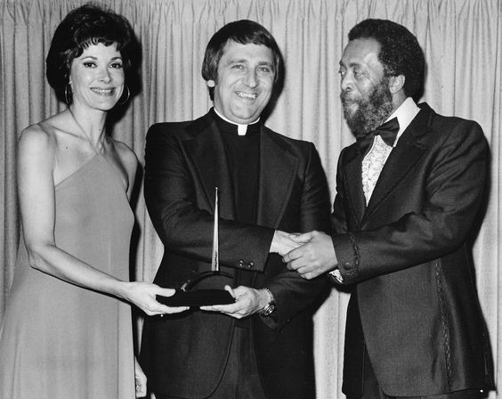 "Paulist Fr. Edward Wrobleski accepting an award for ""Where's Al?"" Franciscans Communications Center, Los Angeles from Jessica Walter and Whitman Mayo at the 15th annual International Broadcasting Awards."